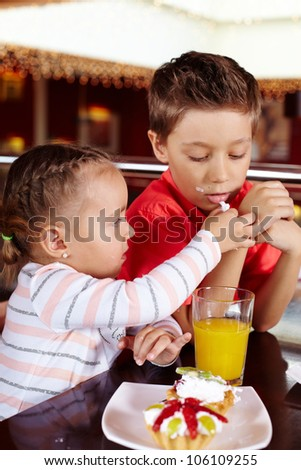 Little girl sharing her dessert with her brother