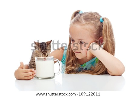 Little girl sharing milk with her kitten - animal care concept, isolated with reflections - stock photo