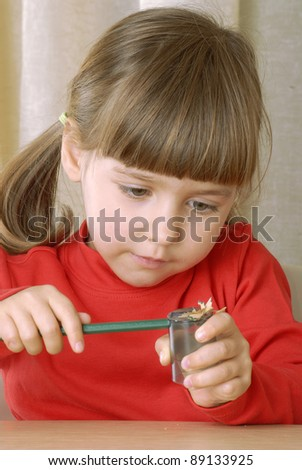 Little girl sharpening a pencil. - stock photo