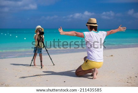 Little girl shooting with camera on tripod - stock photo