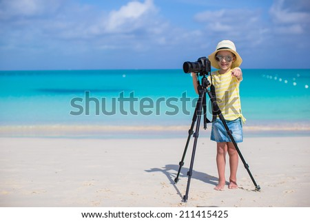 Little girl shooting with camera on tripod during her summer vacation - stock photo
