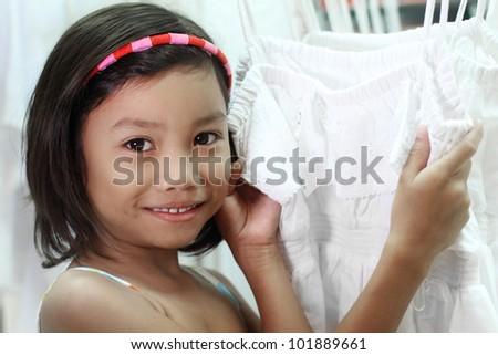 Little girl shopping for a dress - stock photo