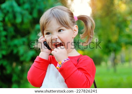 Little girl shouting into the phone in a park. - stock photo