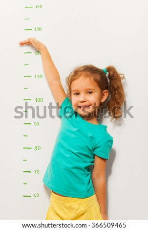 Little girl show how high she will be soon - stock photo