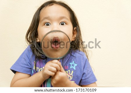Little girl showing mouth through a magnifying glass - stock photo