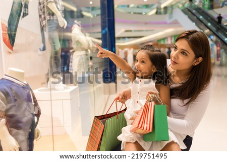 Little girl showing something in the showcase to her mother - stock photo