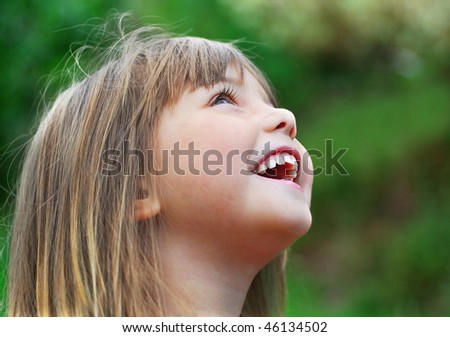 little girl singing and laughing in the garden - stock photo