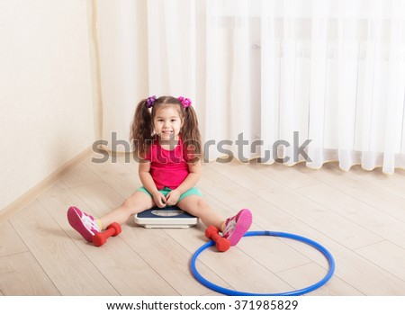 Little girl sit down at floor scales on hardwood floor in living room - stock photo