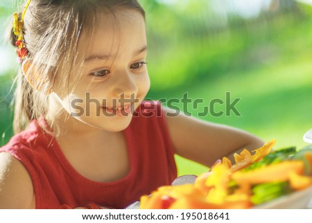Little girl sits at table in garden of parents and eats cut vegetables.