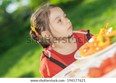 Little girl sits at table in garden of parents and eats cut vegetables. - stock photo