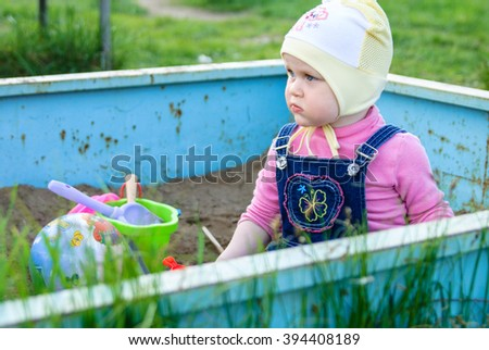 Little girl sits in a sandbox with toys: bucket, shovel, ball - stock photo