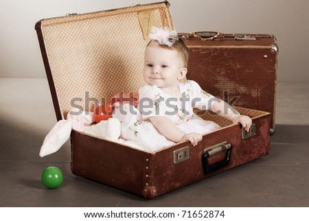 little girl sits in a suitcase. A dark background. - stock photo