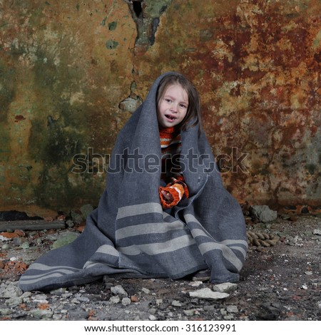 Little girl sits in basement wrapped in blanket and crying with tears on face - orphan, poverty, despair concept - stock photo