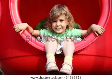 little girl sits in red plastic hole on playground