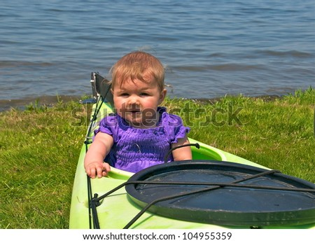 Little girl sits in the back of the kayak waiting for her ride - stock photo
