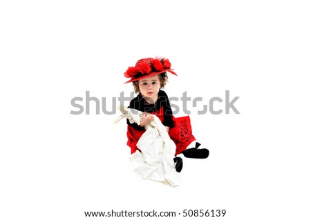 Little girl sits in white room holding an old fashioned rag doll and wearing an old fashioned straw hat. Her dress is black velvet and red tulle with embroidery in black. - stock photo