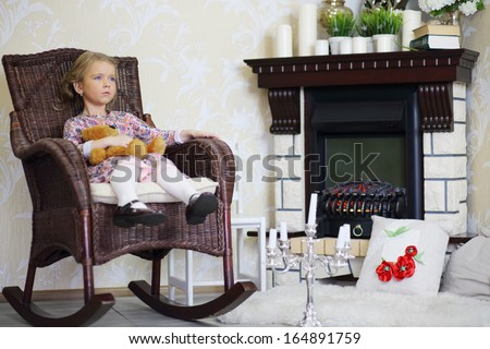 Little girl sits in wicker rocking chair and holds teddy bear near ...