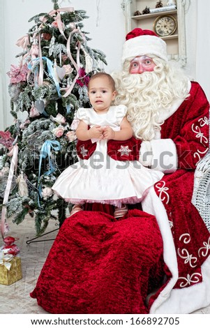 little girl sits on a lap at Saint Nicolas - stock photo
