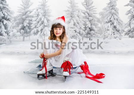 Little girl sits on a sledge and puts on the skates - stock photo