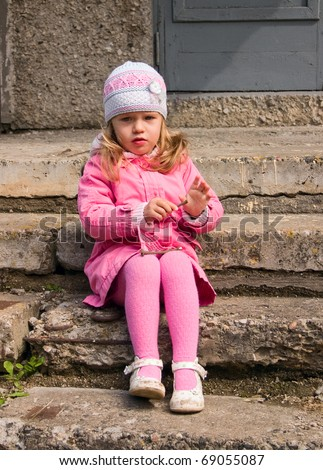 Little girl sits on a stone staircase