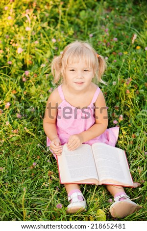 Little girl sits on grass and reads book. - stock photo