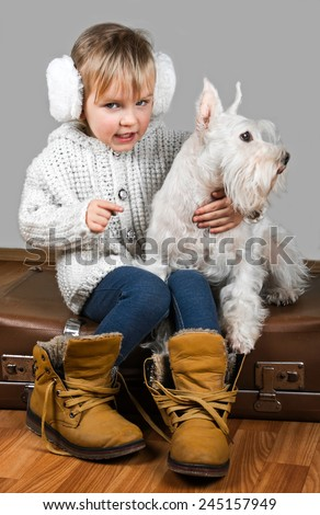 little girl sits on retro a suitcase with dog, ready to winter vacation. - stock photo