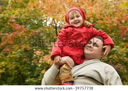 little girl sits on shoulder at man In park in autumn - stock photo