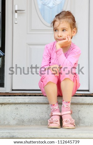 Little girl sits on stairs near white door, smiles frigidly and looks away. - stock photo