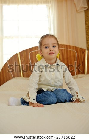 Little girl sits on the bed at home