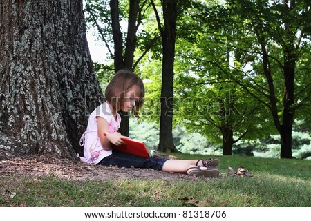 Little girl sits outdoors under a large oak tree and reads a book. - stock photo