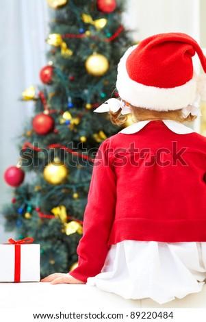 Little girl sitting against Christmas tree. Back view - stock photo