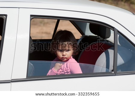 little girl sitting alone in the car and sad