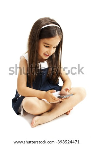 Little girl sitting and playing with smartphone. Isolated on white background - stock photo