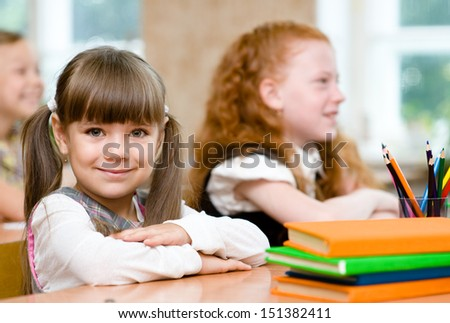Little girl sitting and studying at school class - stock photo
