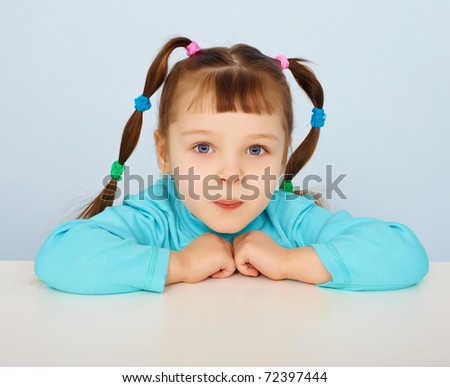 Little girl sitting at a desk on blue background - stock photo