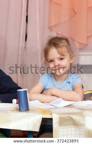 little girl sitting at a school desk
