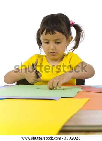 Little girl sitting at desk. Cutting paper with scissors. Front view, white background - stock photo