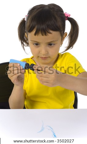 Little girl sitting at desk. Holding blue marker with black turnbutton. White background, front view - stock photo