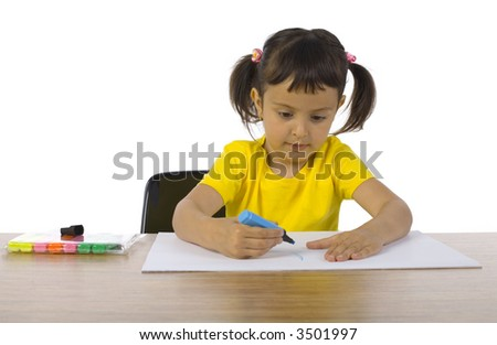 Little girl sitting at desk. Writing something on paper with blue marker. White background, front view - stock photo