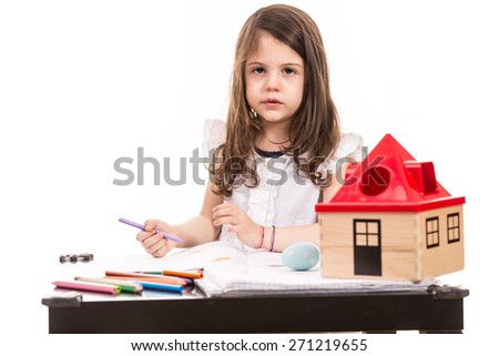 Little girl sitting at table at kindergarten and drawing against white background - stock photo