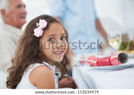 Little girl sitting at table for christmas dinner and looking at camera - stock photo