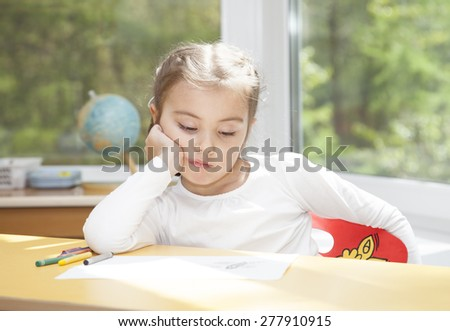 Little girl sitting at the table and thinks about something  - stock photo