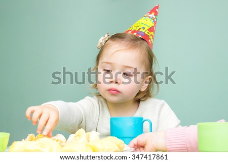 Little girl sitting at the table in her birthday