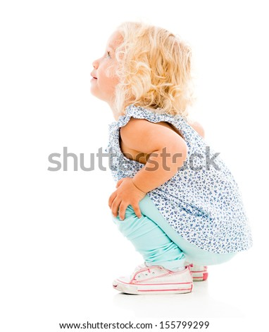 Little girl sitting down and looking up - isolated over white background  - stock photo