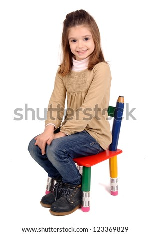 little girl sitting in a chair - stock photo