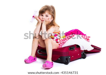little girl sitting in a closed suitcase - stock photo