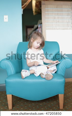 Little girl sitting in a colorful chair looks at or is reading a book.