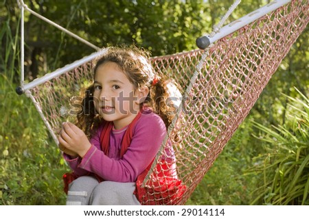 little girl sitting in a hammock in backyard