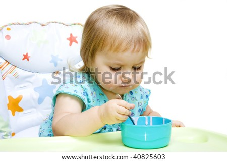 Little girl sitting in baby chair and eating with spoon