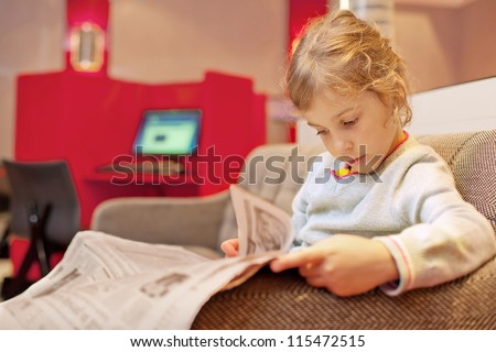 Little girl sitting in chair in cabin big passenger ship read newspaper - stock photo